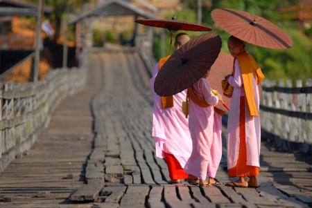 nuns: Burmese nuns.  Alms were walking on a wooden bridge.Bridge of the Mon Sangklaburi near the Burmese border.Sam pra sob river.Sanbkhlaburi Kanchanaburi Thailand. Editorial
