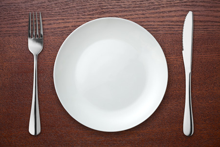 Fork and knife with white plate on wooden table