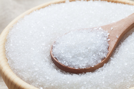 White sugar with spoon in wooden bowl, Close-up.