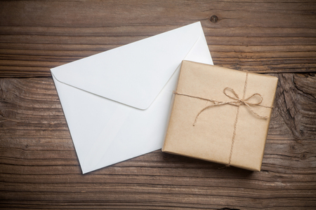 packaging box: Gift box with brown paper and envelope on wooden table Stock Photo