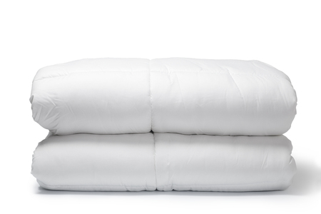 Warm and confortable folded white quilt on white background