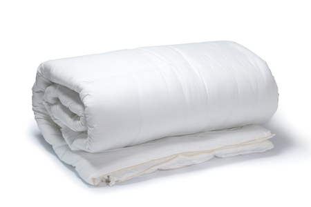 bedding: Warm and confortable folded white quilt on white background