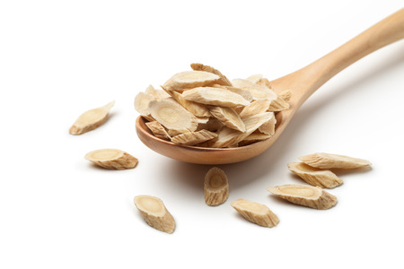 Sliced of Astragalus (Huang Qi) in a wooden spoon, isolated on white background. Chinese herbal medicine. Stockfoto