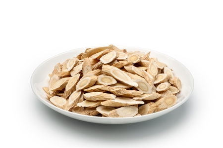 Sliced ​​of Astragalus (Huang Qi) in a ceramic dish, isolated on white background. Chinese herbal medicine.
