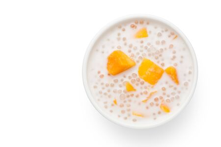 A bowl of sweet sago cream with mango and coconut milk on white background. Top view.
