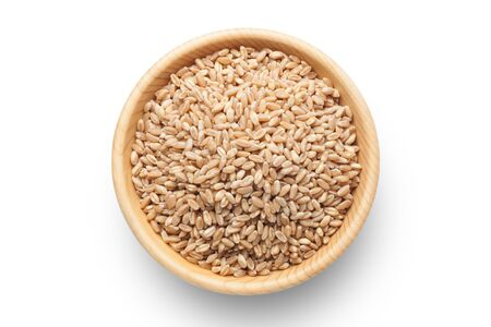 Wheat grains in a wooden bowl isolated on white background. Imagens