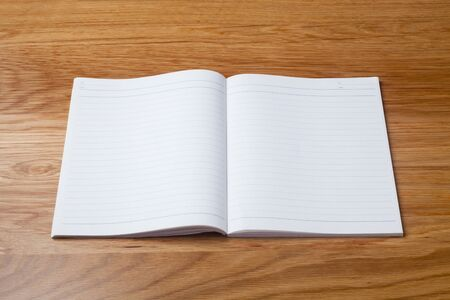 Blank notebook on wooden table Imagens