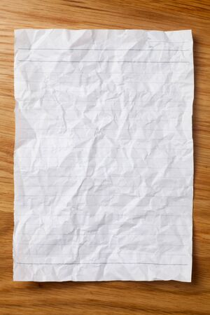Rumpled lined sheet of paper on wooden table. Top view. Imagens