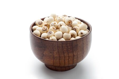 Dried lotus seeds in a wooden bowl isolated on white background