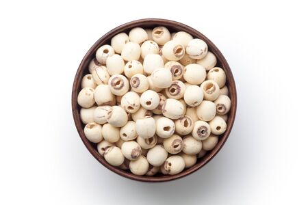 Dried lotus seeds in a wooden bowl isolated on white background. Top view.