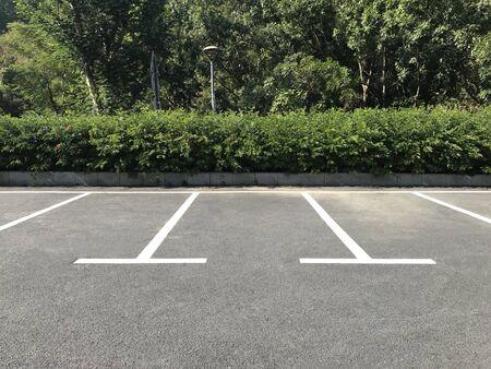 Plaza de aparcamiento exterior vacía. Estacionamiento de automóviles con marca de líneas blancas.