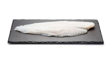 Basa fish fillet on a black stone plate, Isolated on white background.