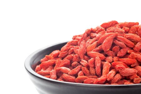 Dried goji berries (Chinese wolfberry) in a black bowl, Isolated on white background. Close-up. 스톡 콘텐츠