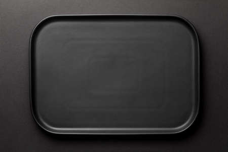 Top view of empty black plate on black background