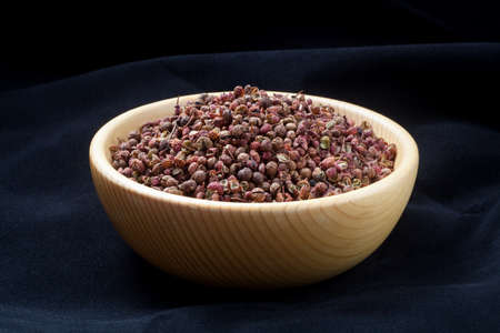 Sichuan pepper (zanthoxylum bungeanum) in a wooden bowl. Chinese prickly ash. 版權商用圖片