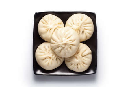 Fresh baozi (Chinese steamed buns) in a black ceramics plate. Isolated on white background. Top view.