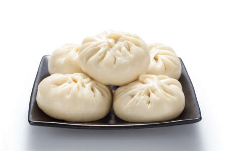 Fresh baozi (Chinese steamed buns) in a black ceramics plate. Isolated on white background.