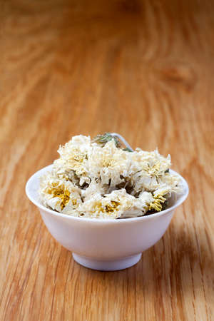 dried chrysanthemum flowers in a ceramic cup on the table