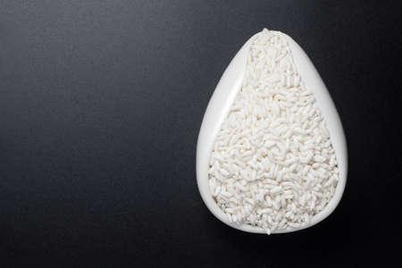 Glutinous rice in a ceramic spoon on black background. Top view. 版權商用圖片