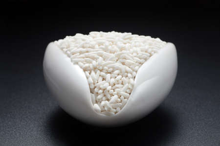 Glutinous rice in a ceramic spoon on black background.