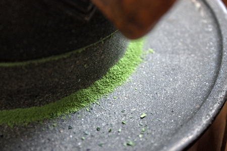 Détail de poudre de thé vert finement broyé, moulin en pierre Banque d'images