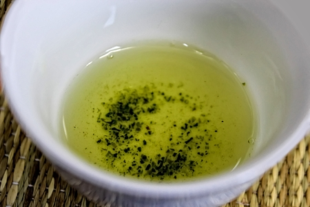 sencha: Detail of cup of green matcha tea on table