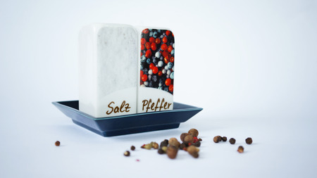 Ceramic pepperbox and salt cellar with pepper corns isolated on white Stock Photo