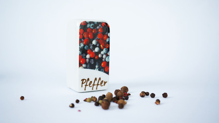 pepperbox: Ceramic pepperbox with pepper corns isolated on white