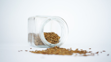 Glass jar with cumin isolated on white