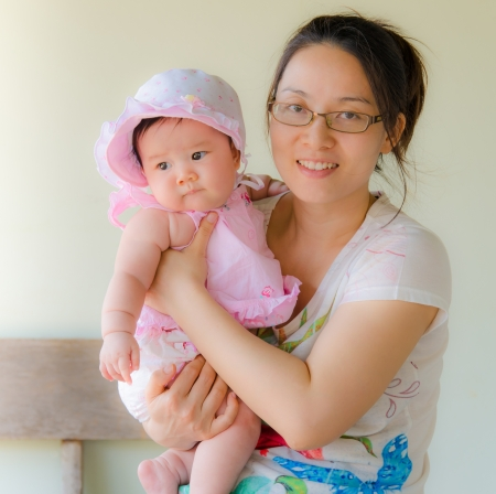 happy glasses mother holding sweet baby girl with pink dress photo