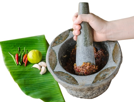 pounding: hand pounding shrimp paste chilli sauce in mortar with ingredient on banana leaf -thai style