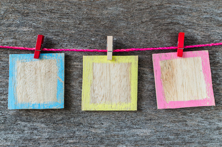 wooden picture frame hanging on clothesline on wood background. photo