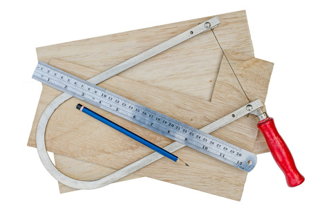 fret: manual fret saw and plywood  with ruler and pencil on white background