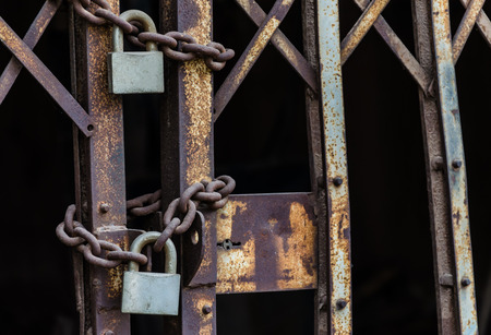 rusty chain and master key locked on grunge iron gate photo