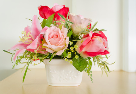 flower arrangement: Decoraci�n artificial de color rosa-flor hermosa rosa en bote blanco.