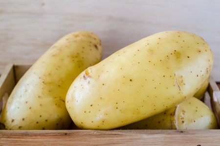 Close up of potatoes on wooden background. photo