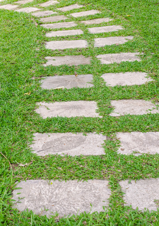 Stone path on green grass in the garden photo