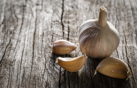 Garlic bulb and cloves on wooden background photo