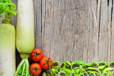 Daikon radish,tomatoes on the wooden background photo