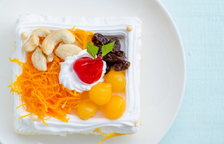 butter icing: Piece of cake with cashew nut, raisin and Thai sweetmeat made of egg yolk on wooden table. Stock Photo