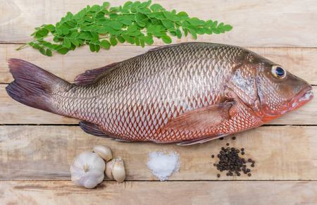 Fresh red snapper preparation with spices and herbs on wooden table.