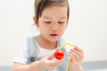 little asian girl playing rope and ball