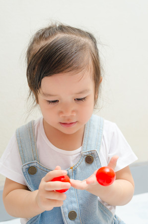 pratice: little asian girl playing little red balls