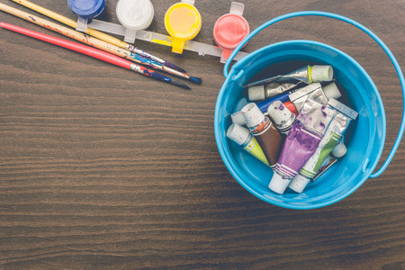 artist: Vintage artists brushes and paint tubes on wooden table. Stock Photo