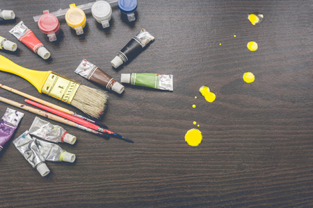 painter: Vintage artists brushes and paint tubes on wooden table. Stock Photo