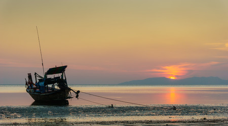 puckered: sunset on the beach with old wooden fishing boat in Trang province,Thailand