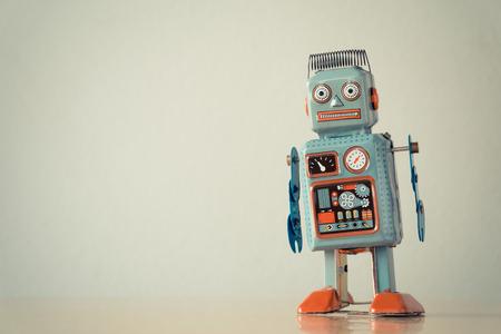 Vintage tin toy robot on wooden table.
