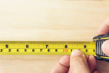 cintas metricas: Hand holding a tape measure on the brown wooden background