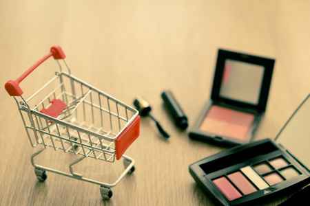 elastic garments: Shopping cart with cosmetics on wood background.