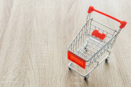cart: Shopping cart on wooden table.